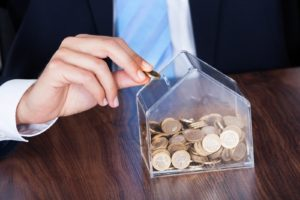businessman-inserting-euro-coin-in-money-box